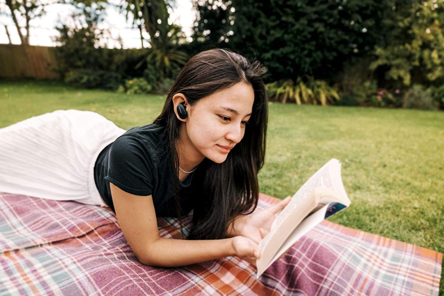woman with earbuds reading a book