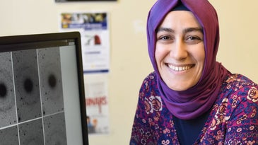 Burçin Mutlu-Pakdil in front of a computer screen with galaxy images