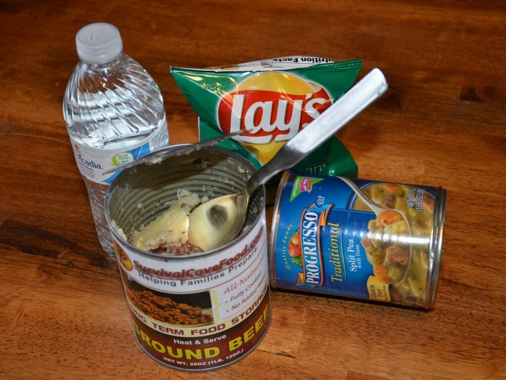 An assortment of canned goods and chips and bottles of water.