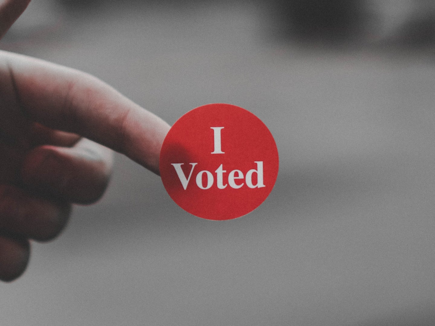 """a person holding an """"I Voted"""" sticker on their finger"""