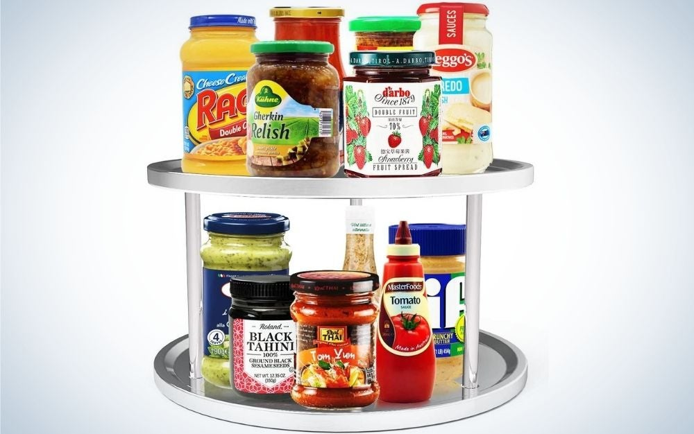 A turntable cabinet with two floors and white color and oval shape which on both floors has jars with different sauces and relays and different colors as well.
