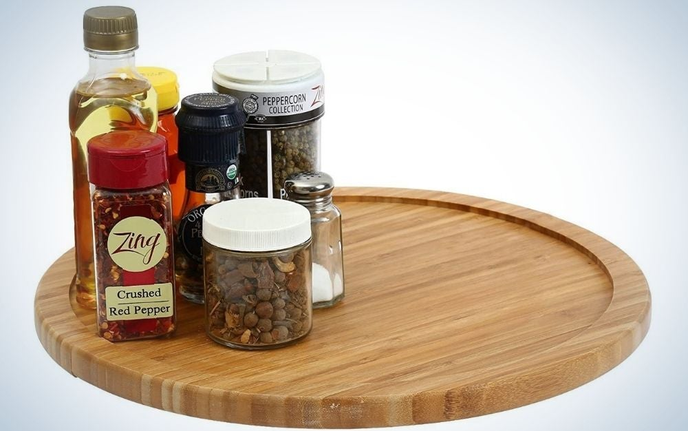A round turntable cabinet and wooden color as well as a series of jars with spices and different flavors.