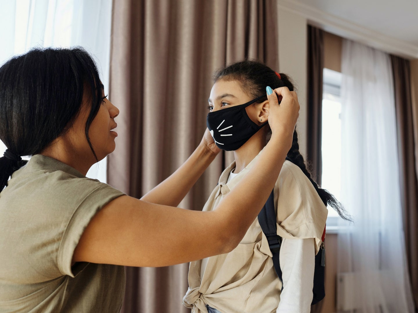 parent putting mask on their child