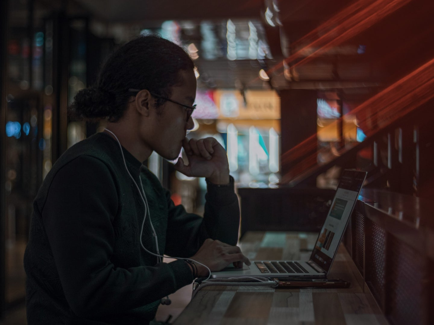 a person sitting in a cafe at night, using a laptop