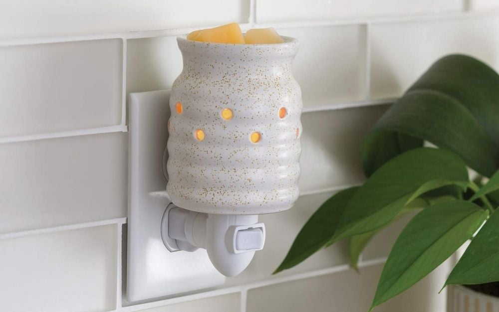 White candle warmer pugged in the outlet