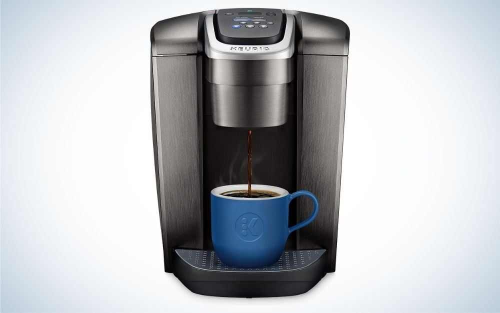 Brushed slate coffee maker and a blue cup getting filled with coffee