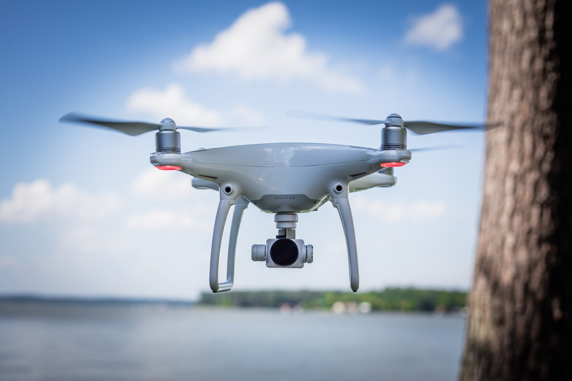 a drone hovers next to a lake and a tree
