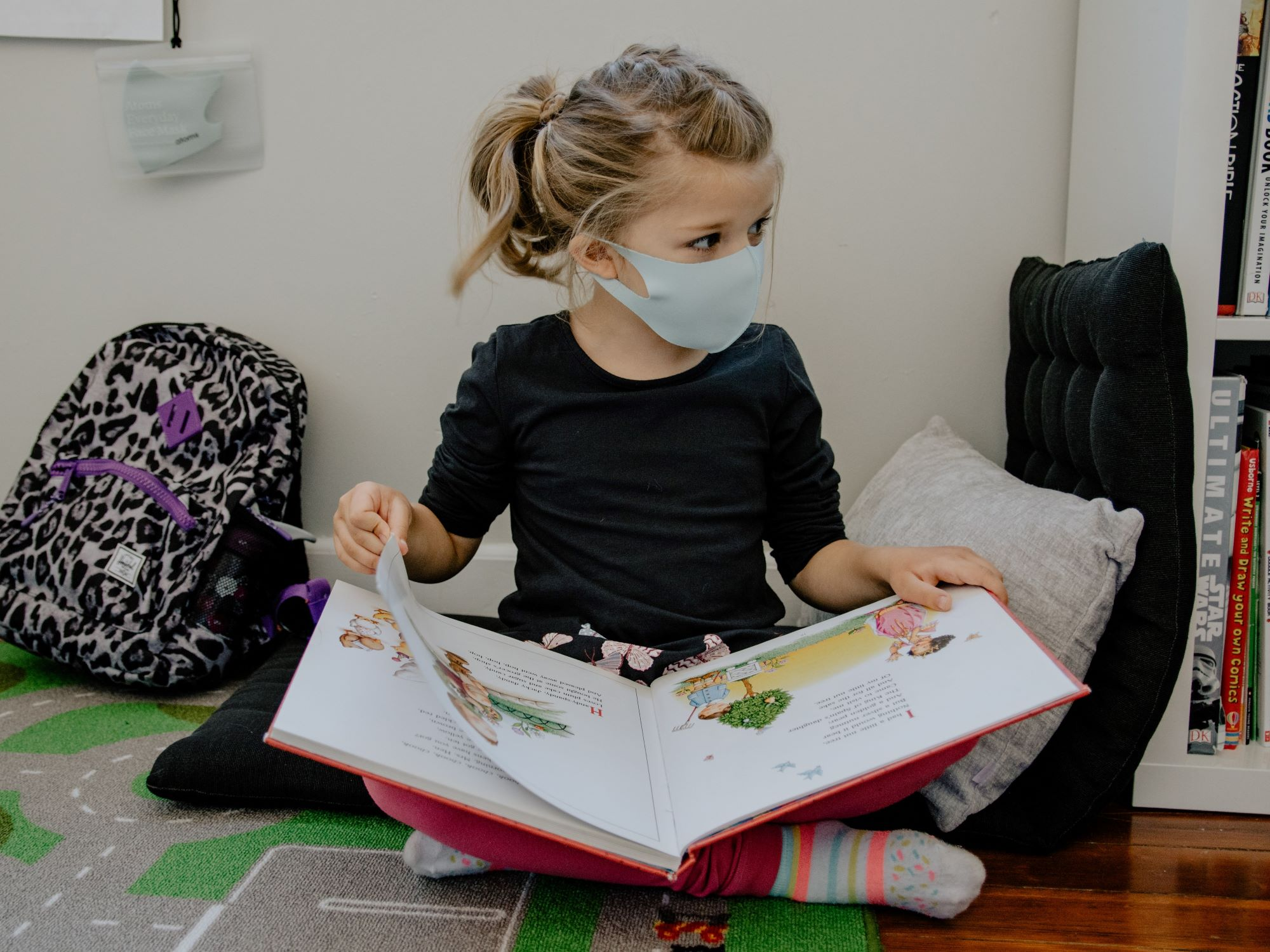 A child wearing a mask reading a picture book