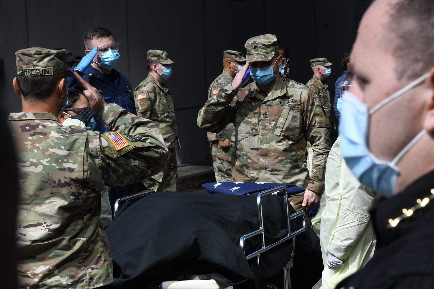 National guard members salute a veteran who died from COVID-19 at the Javits Center field hospital in New York City
