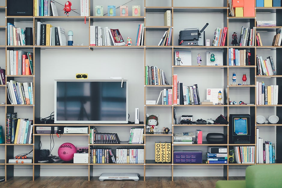 media console with gadgets, books, and a TV
