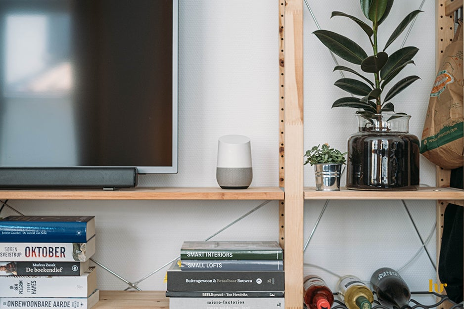 TV, smart speaker, wine, and books on a media console