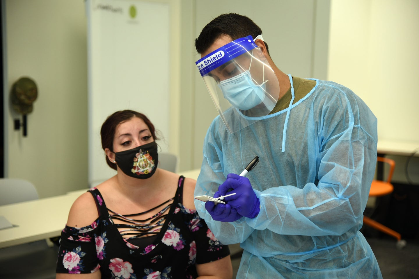 National guard members assist with point-of-care testing in Tempe, Arizona wearing face shields and plastic suits