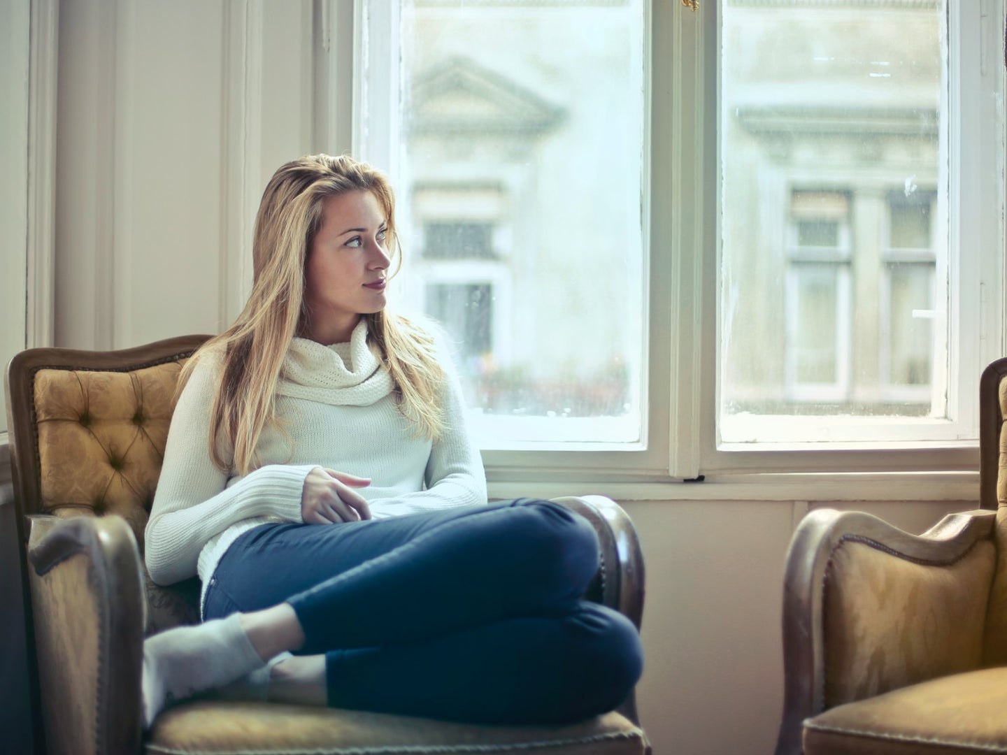 a blonde woman sitting in a chair by a window in a white sweater and jeans