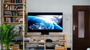 TV on a stand next to bookshelf