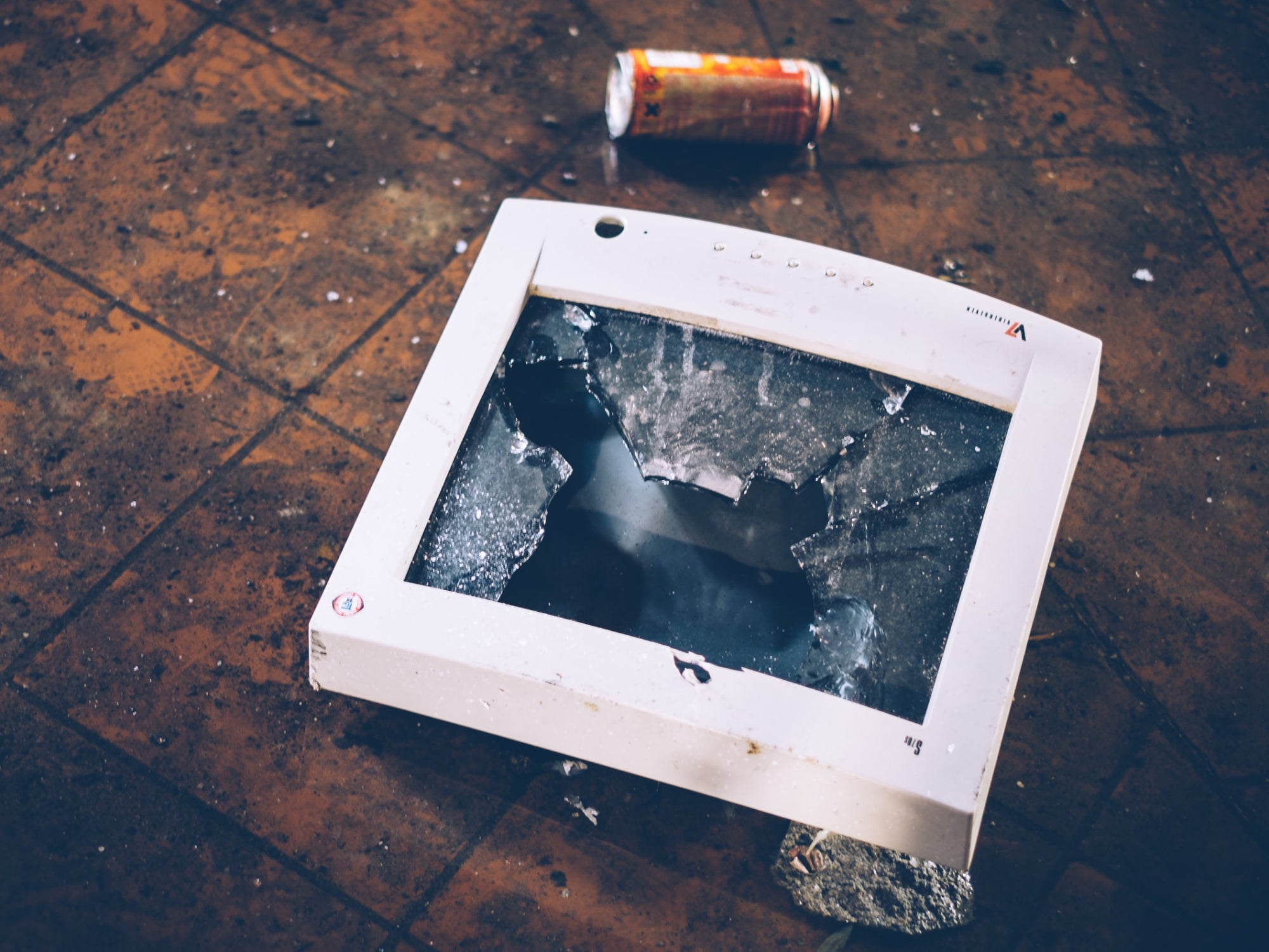 a smashed computer monitor on a floor near a discarded can