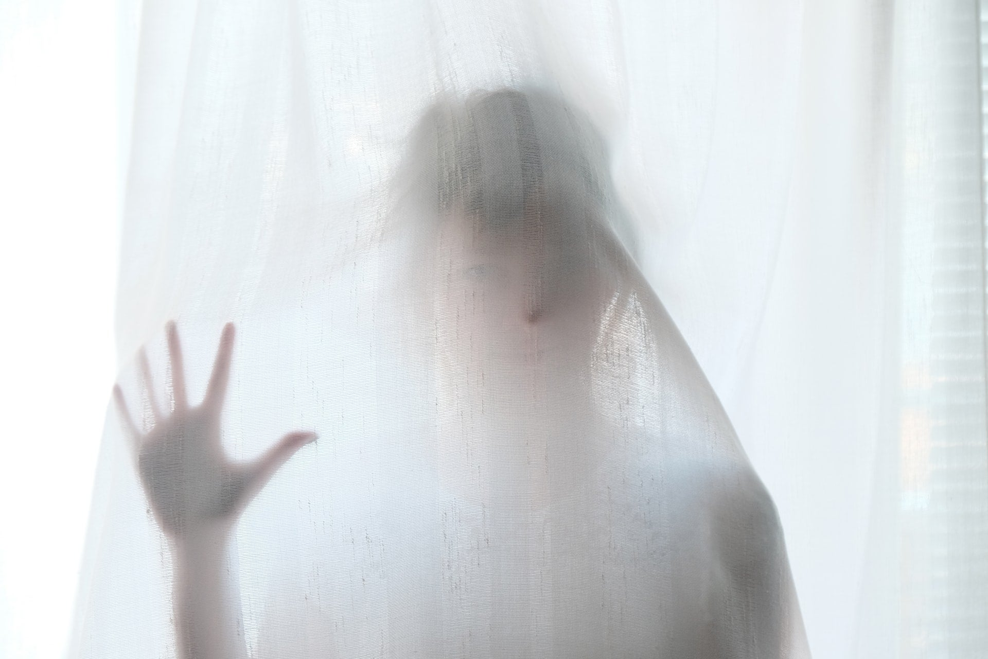 A person stands behind a white gauzy curtain in a spooky fashion