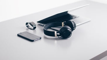 headphones, laptop, and phone on a table