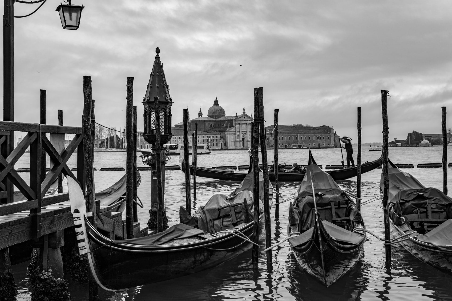 A black and white photo of gondolas in Venice