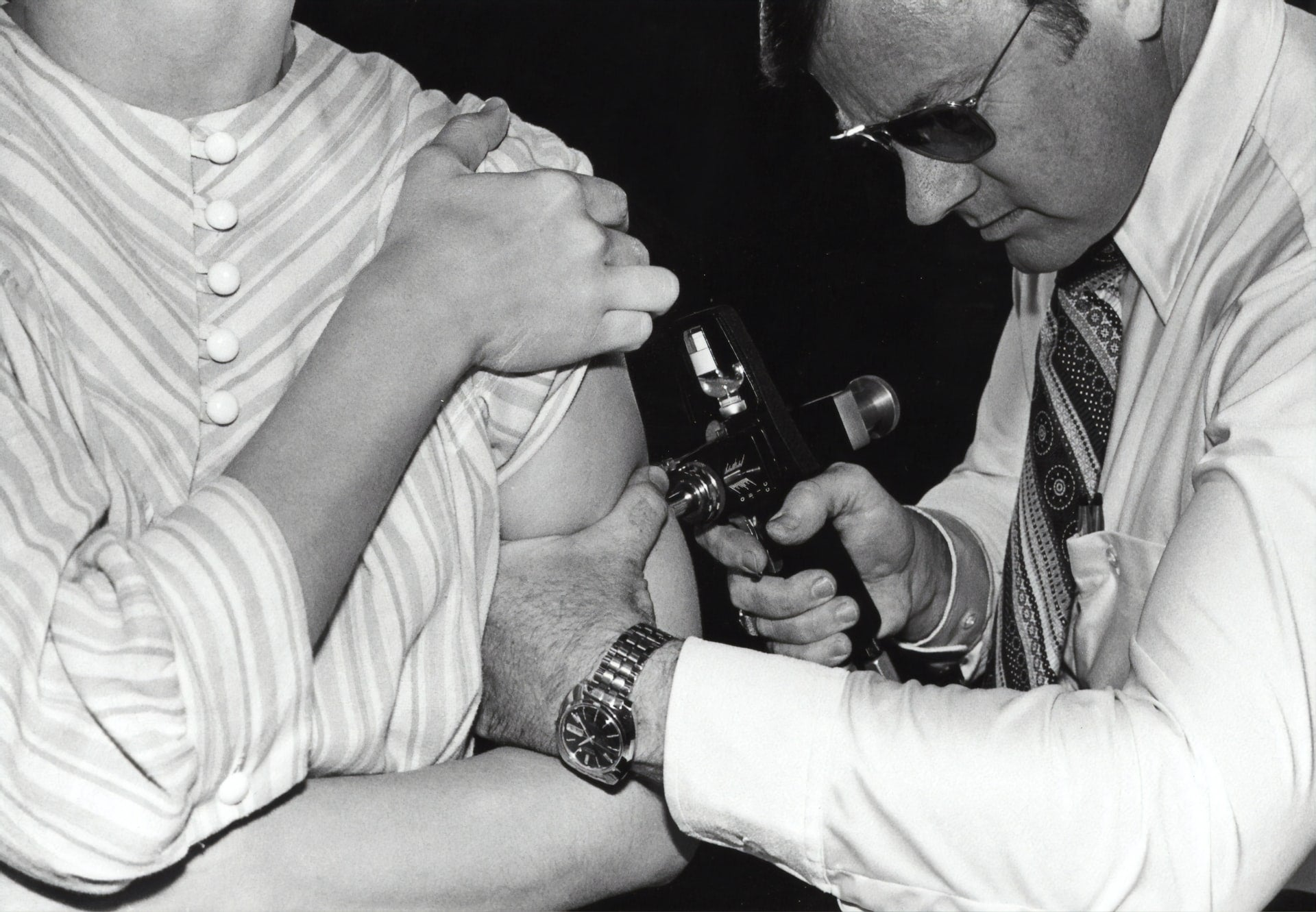 Black and white photo of a patient getting a swine flu vaccine through a jet injector in 1976