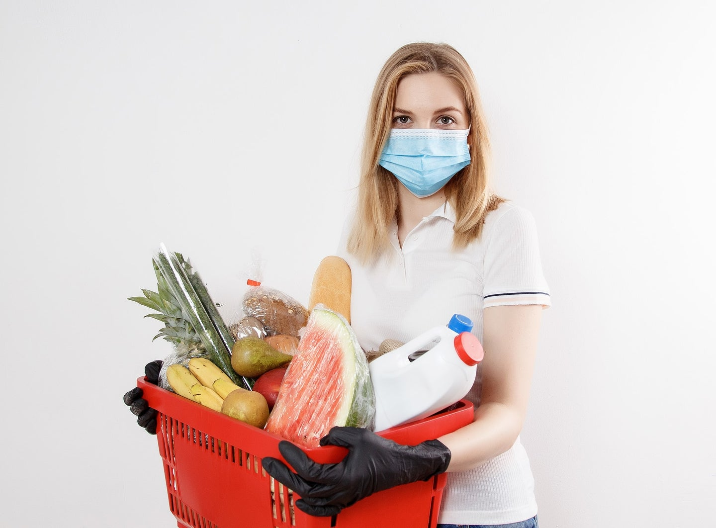 Person in a mask and disposable gloves holding a basket of groceries