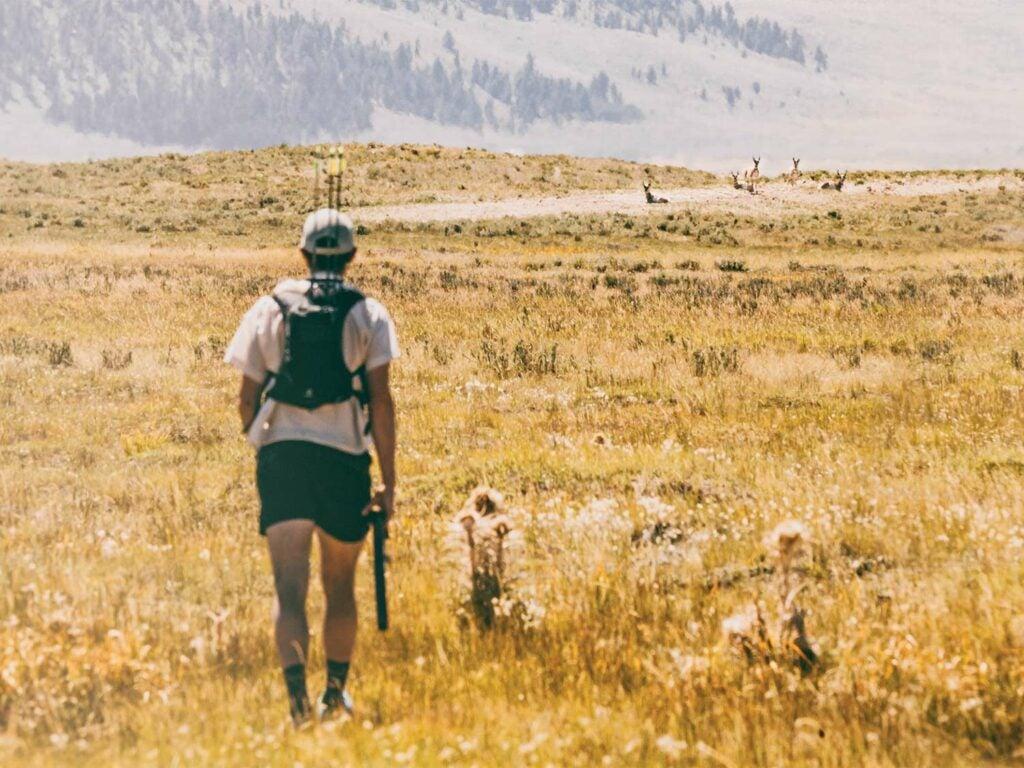 A hunter walks through a large open field after a herd of antelope.