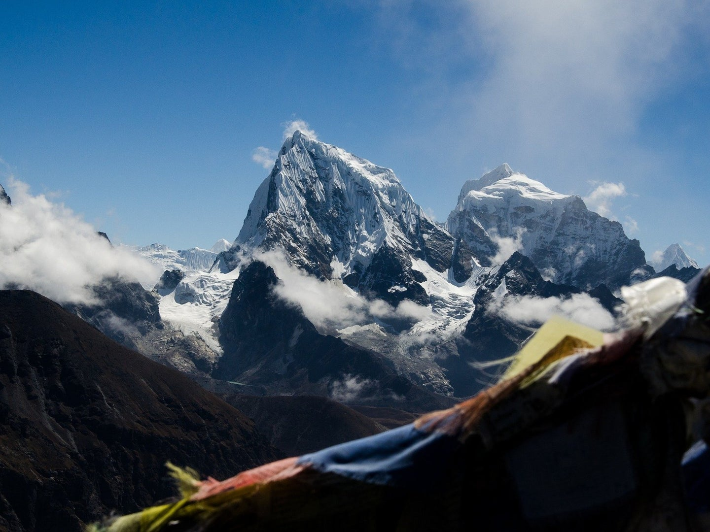 A photo of Mount Everest behind clouds and under a blue sky.