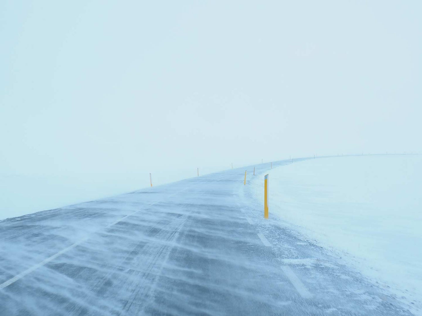 An image of a road covered in snow during a blizzard.