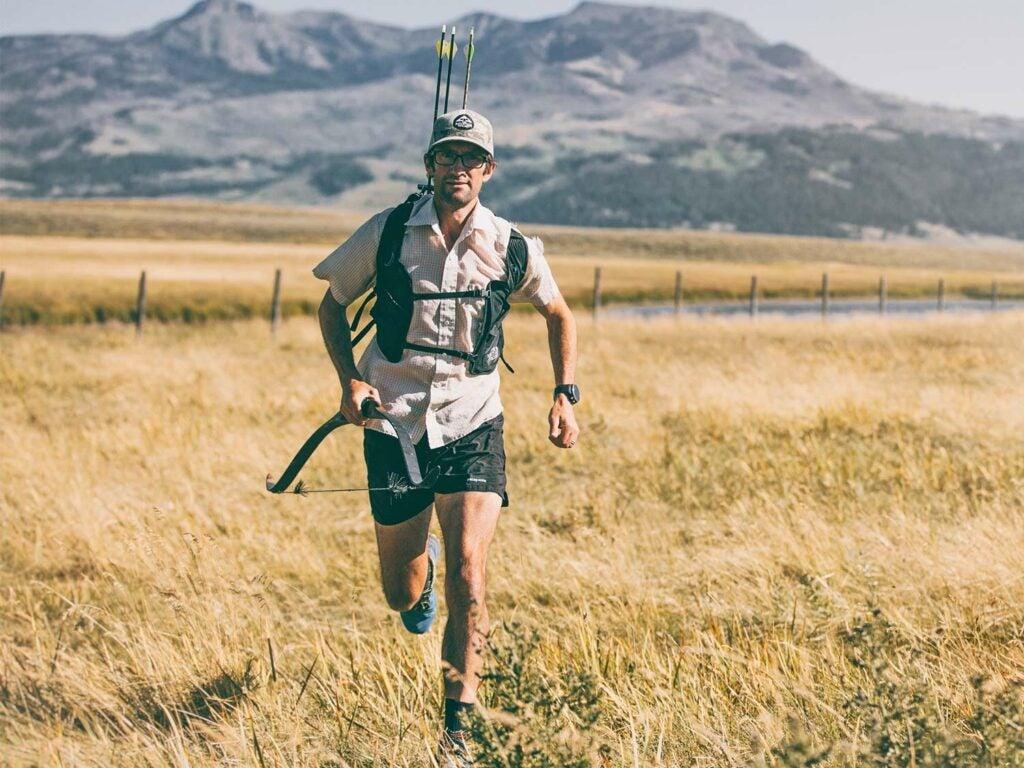 A man runs through an open field carrying a traditional bow.