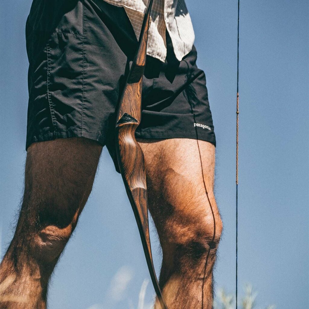A hunter in shorts holds a traditional bow during a stalk and run hunt.