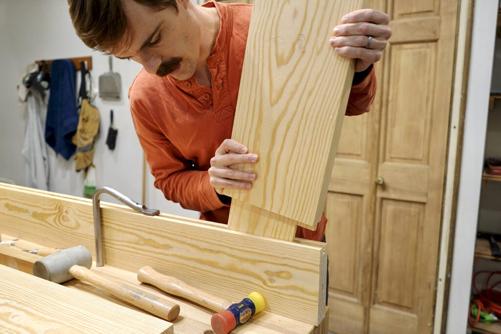 a person fitting a mortise and tenon joint as part of building an exterior door