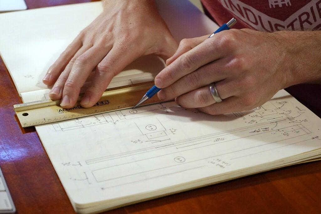 a person drawing plans for an exterior door in a notebook