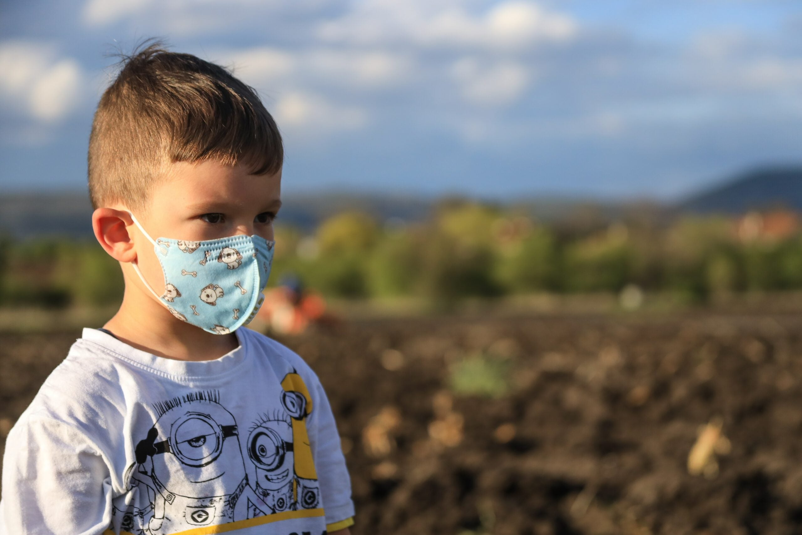 A kid with a cartoon-themed mask standing in a field
