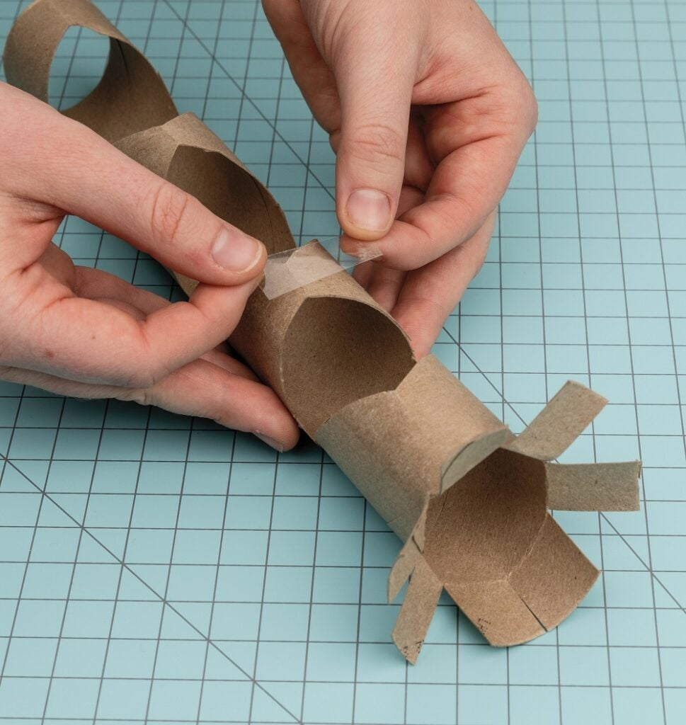 Taping the diamond-shaped holes in the paper towel rolls
