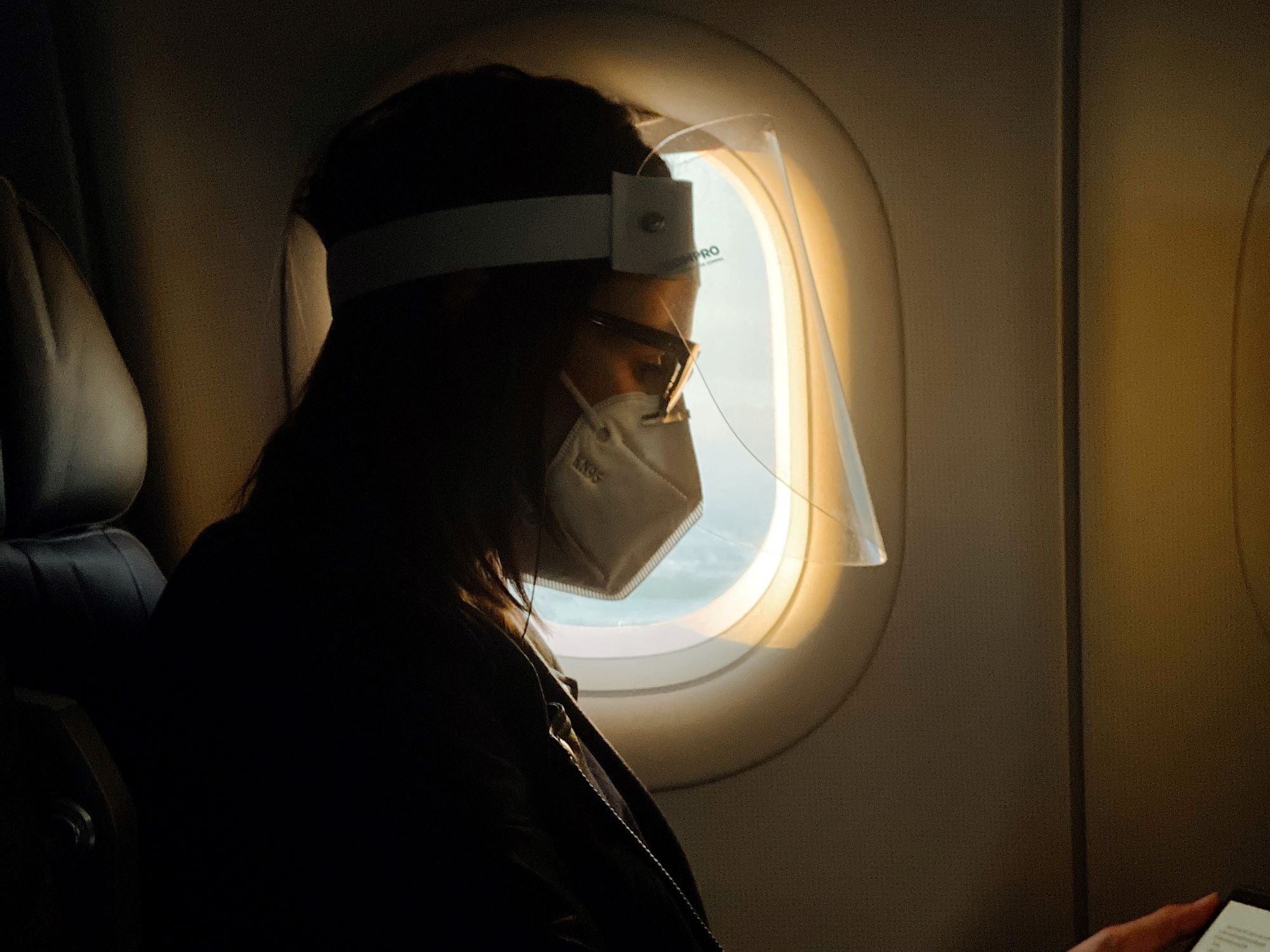 A woman wearing a face mask and face shield on an airplane