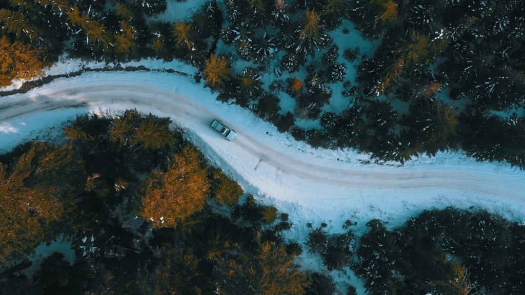 Birds-eye view of a car on a snowy road, flanked by trees.