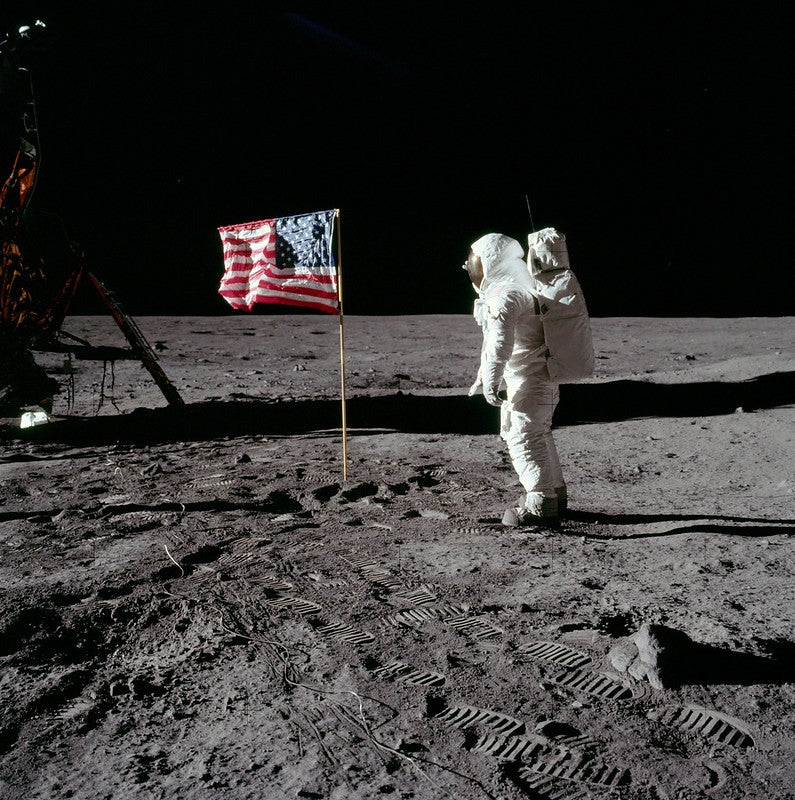 an astronaut stands next to an american flag on the moon