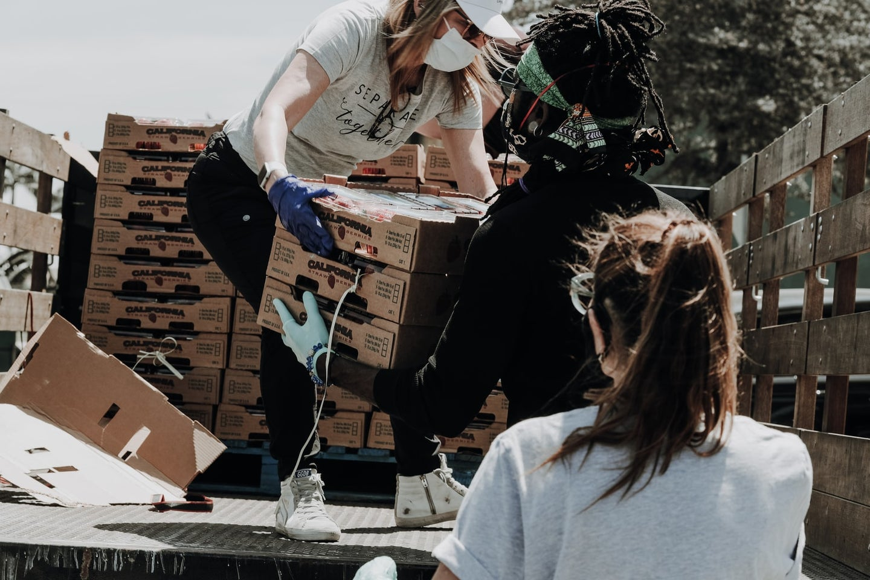 Volunteers gathering food off of a truck.