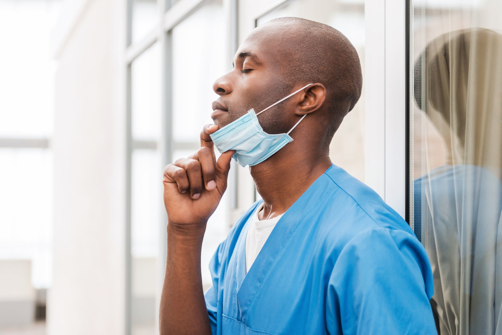 A surgeon in scrubs pulling a mask off their face