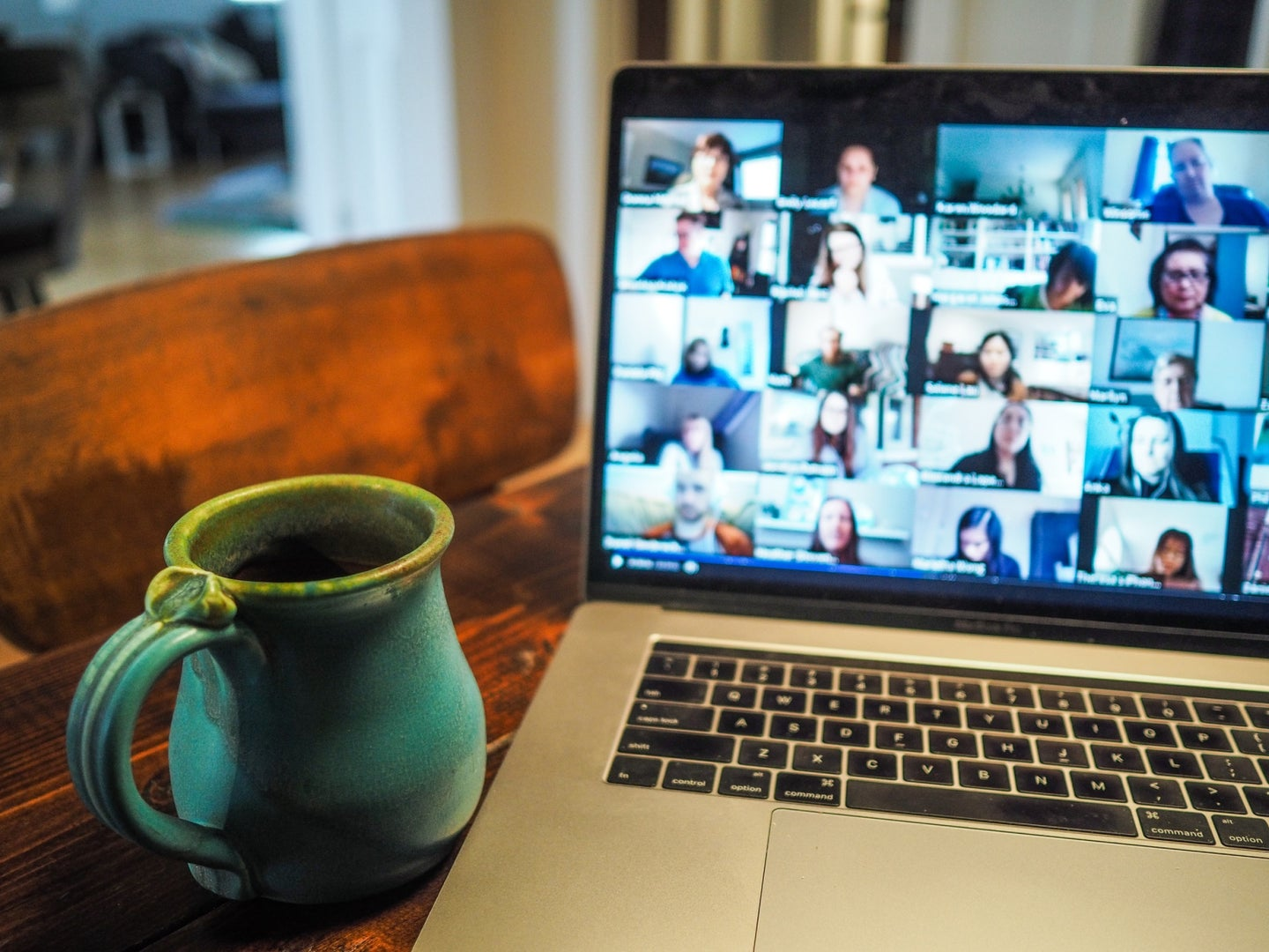 a mug of coffee or tea next to a laptop with Zoom open