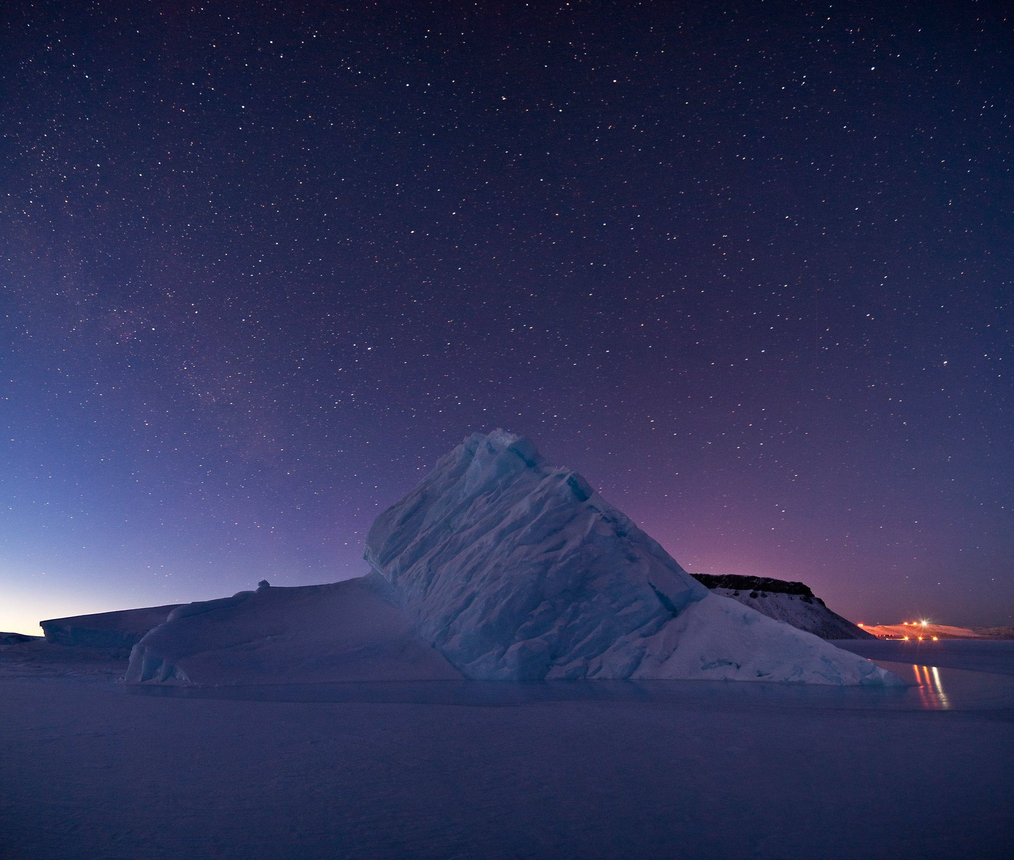 The starry Arctic sky over an iceberg in Greenland