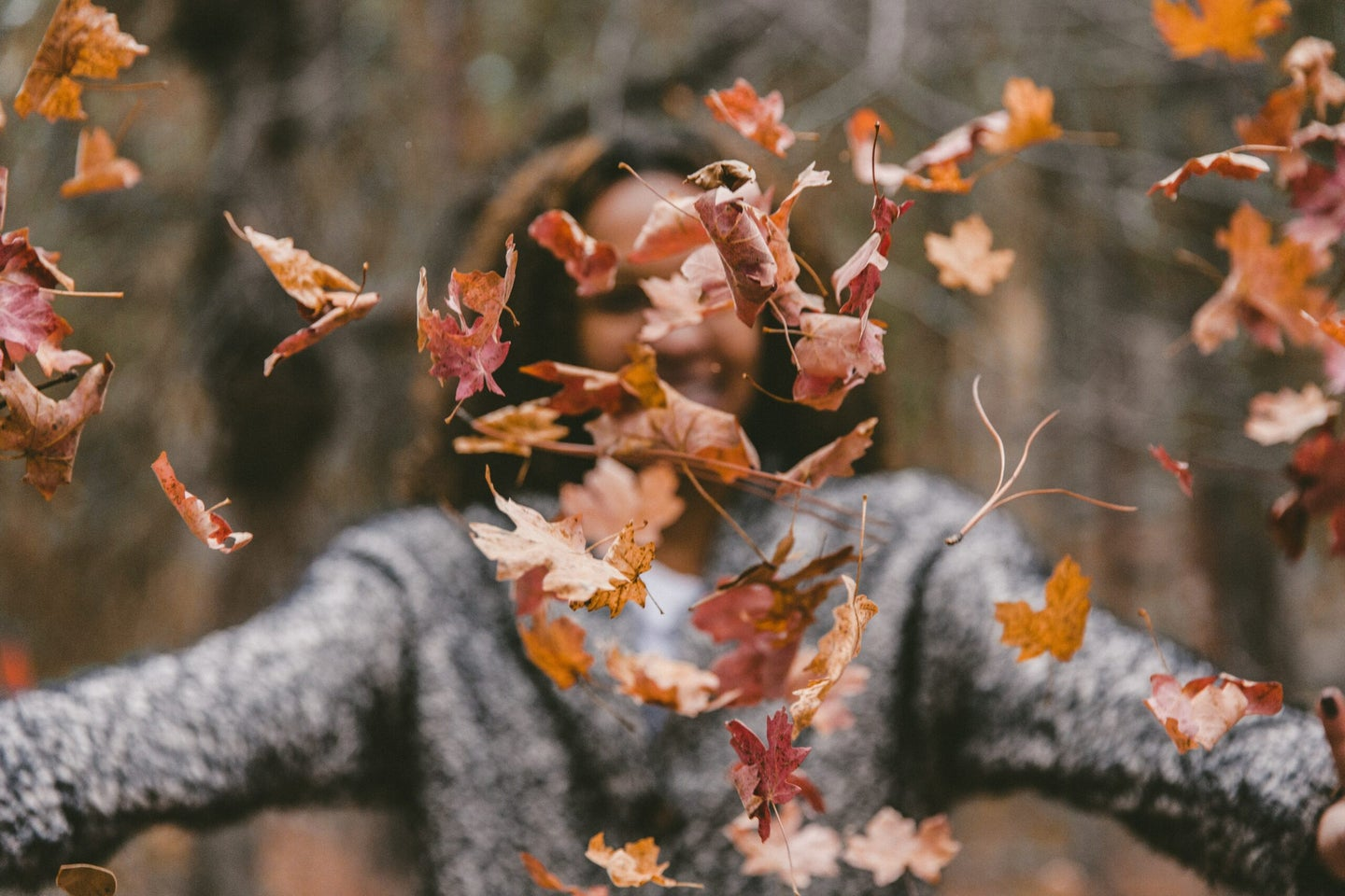 a woman throws fall leaves into the air while smiling