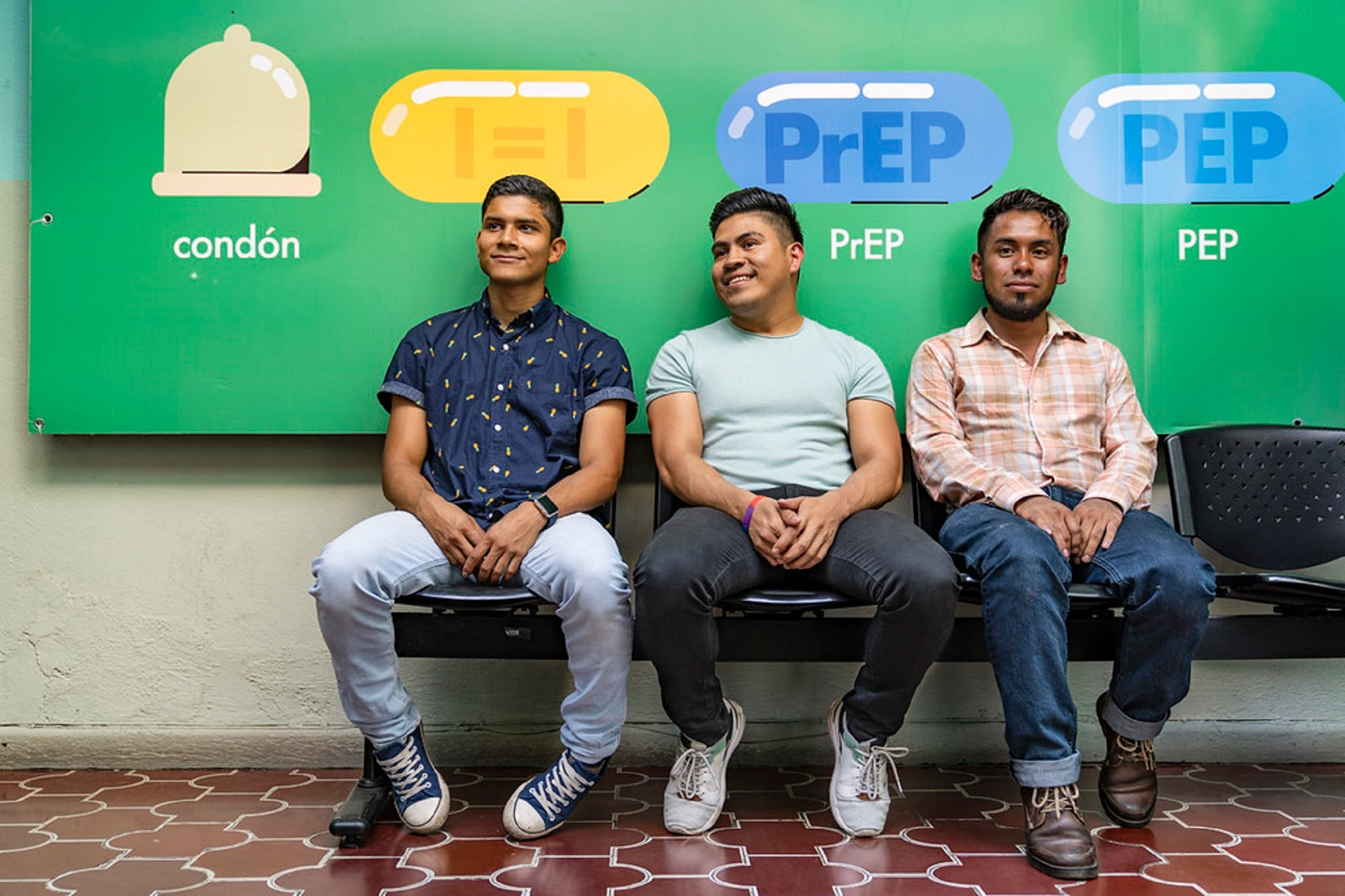 Three staff members sit at a free HIV clinic in Guatemala City with green PrEP banners in the back