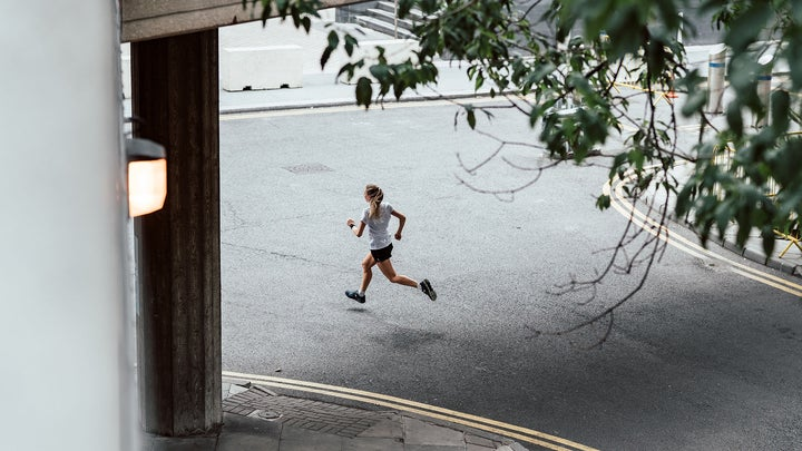 Person running down the street in the best running shoes.