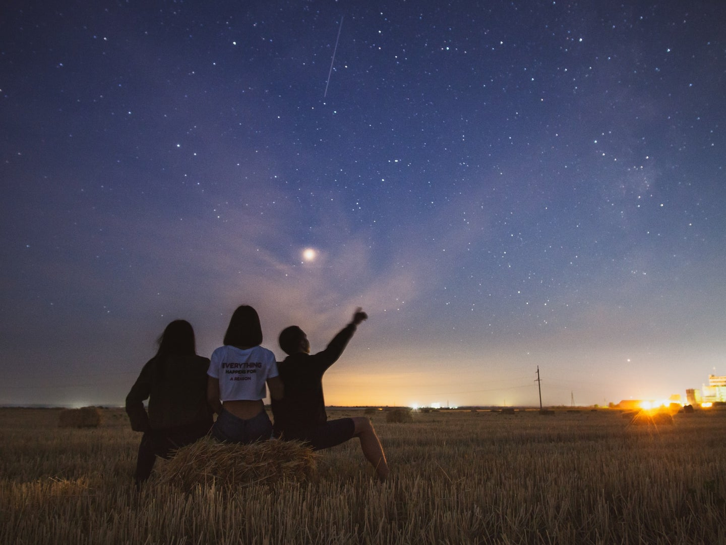 Three people watching the night sky while sitting on a hay bale in a field