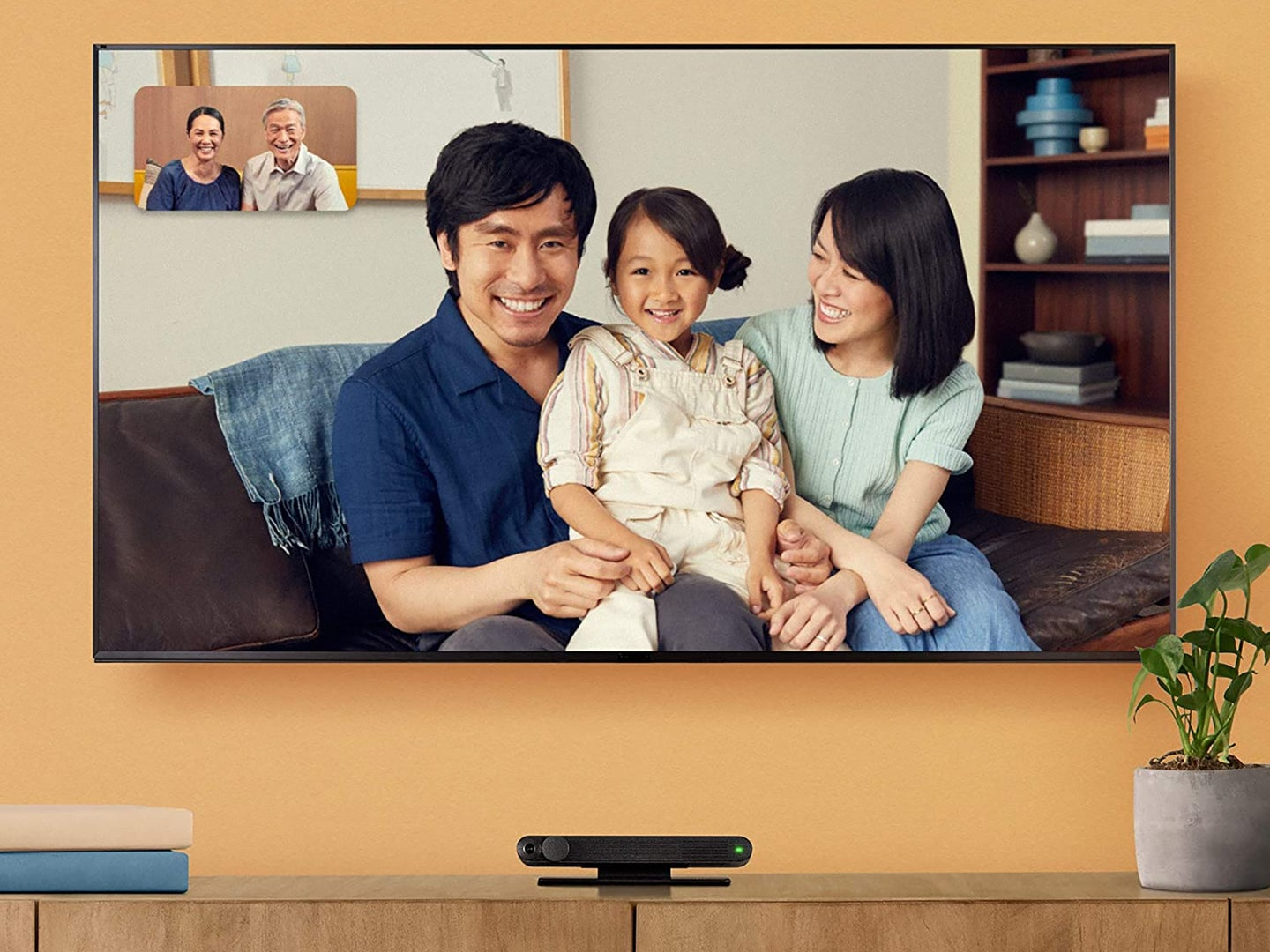 a TV with a family video chatting on it over a video call