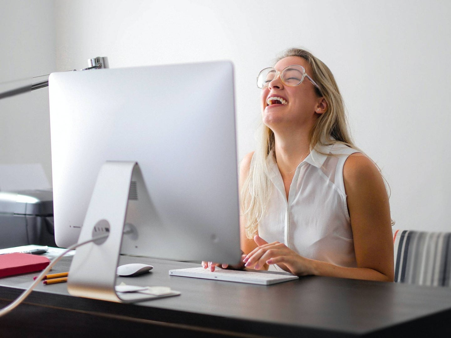 Person laughing at computer