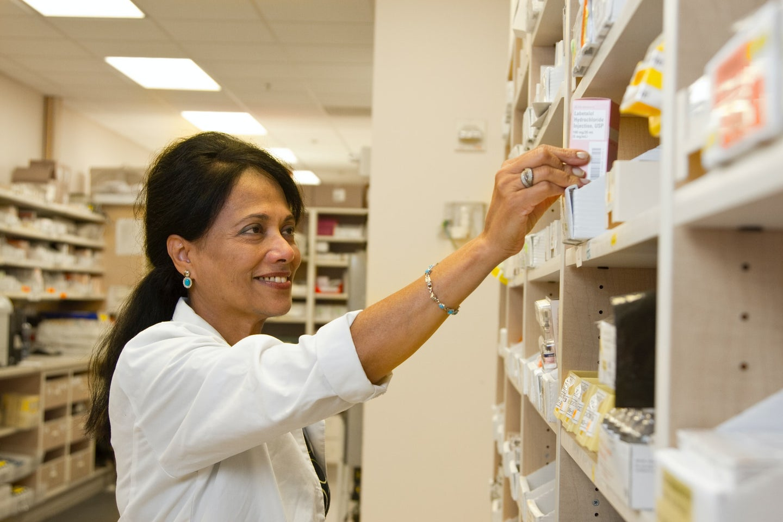 A pharmacist picking a medication off a shelf