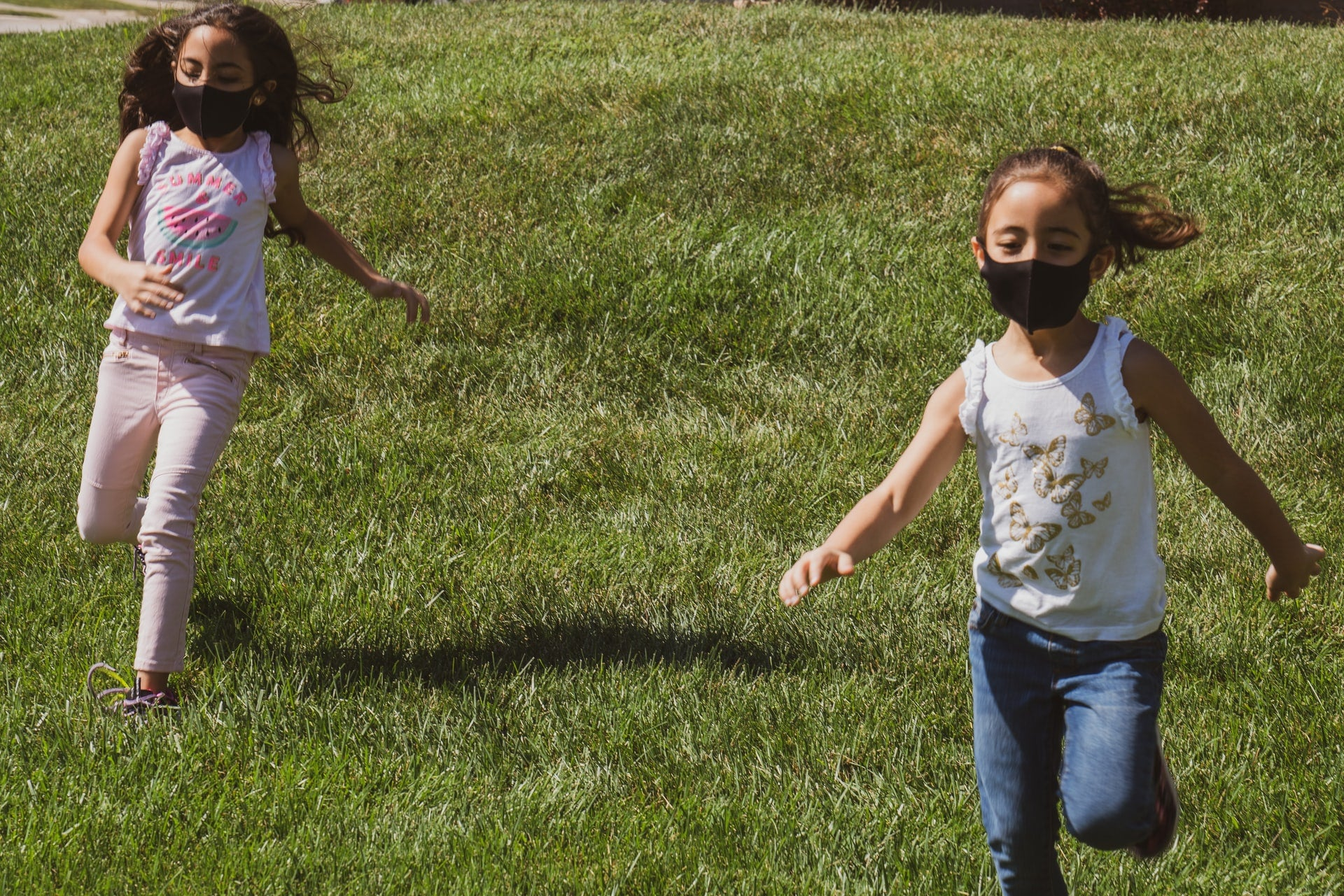 Two kids running on a lawn with masks on