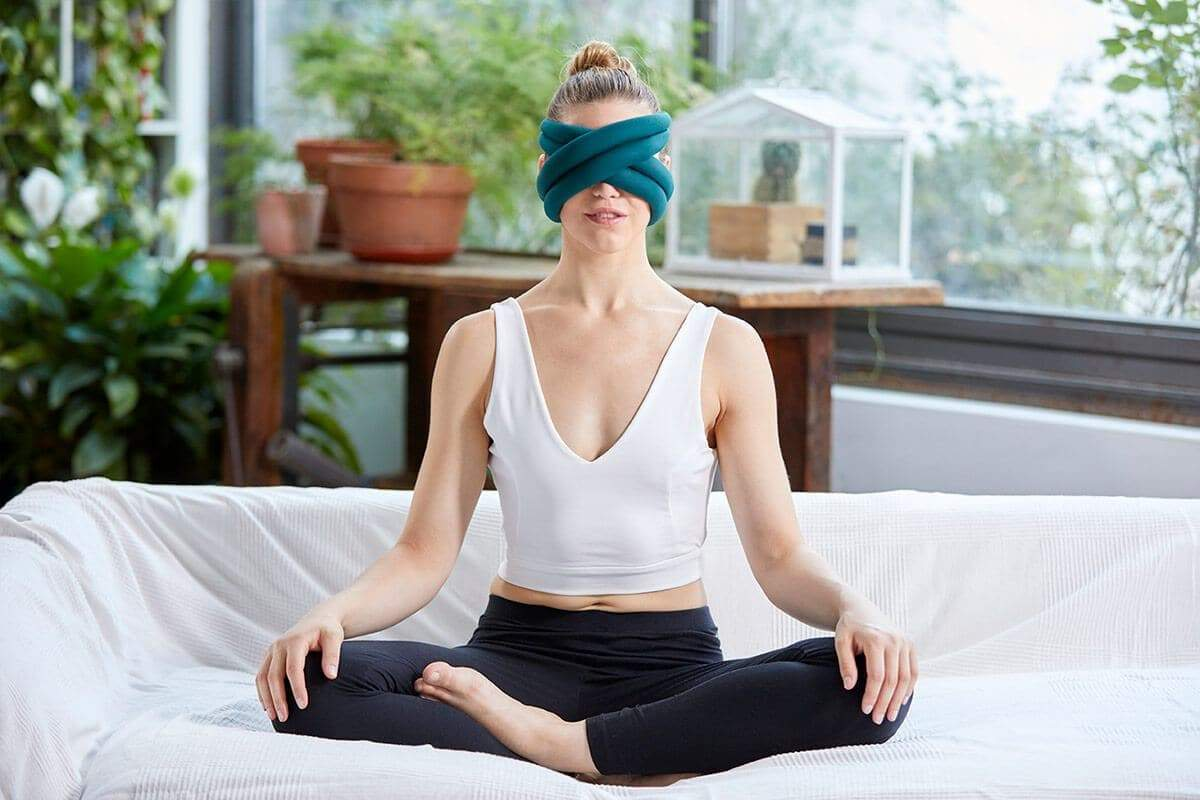 a woman sits cross legged with a blue mask wrapped around her head