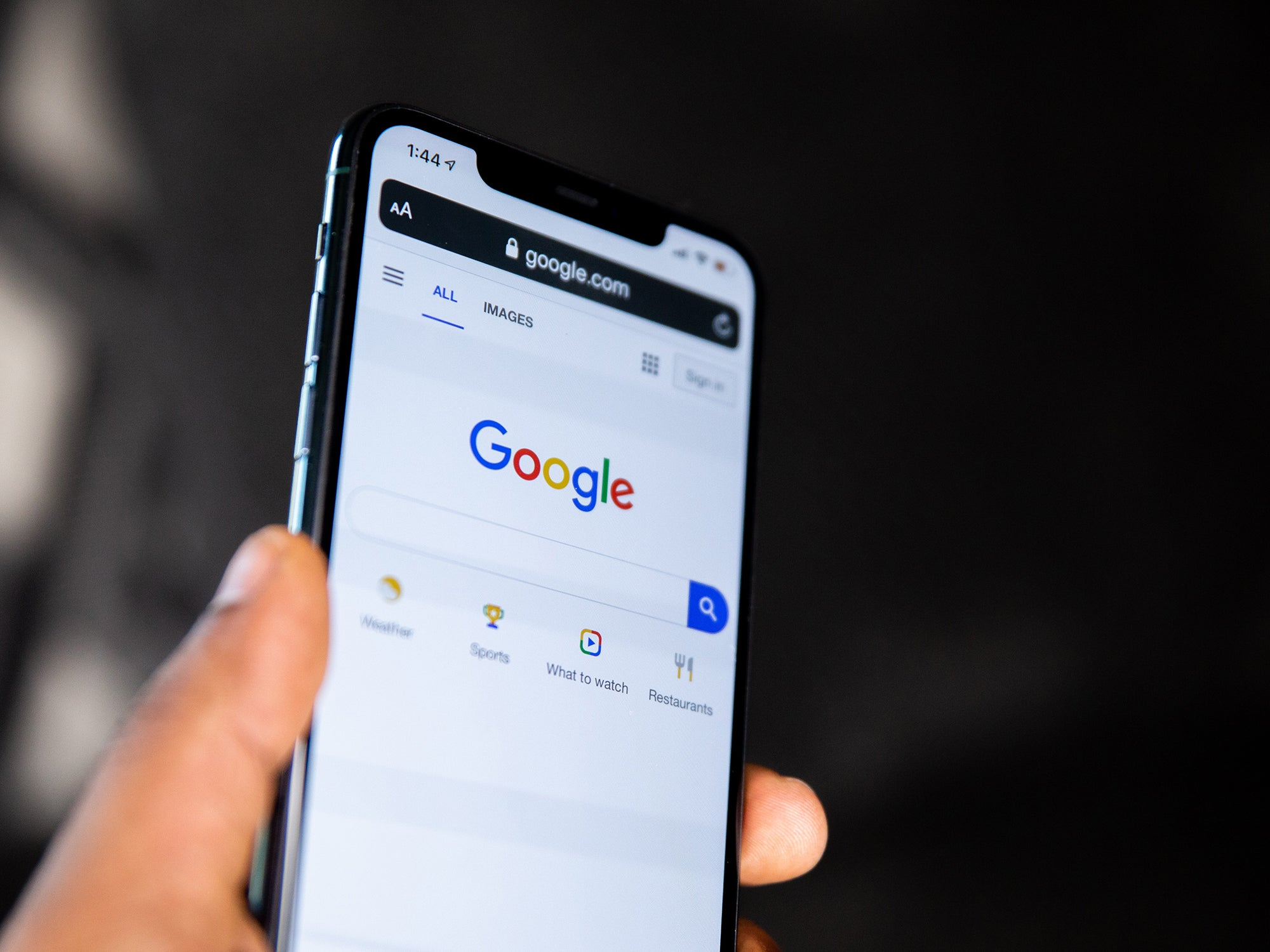 an Apple iPhone with the Google search engine up on the screen